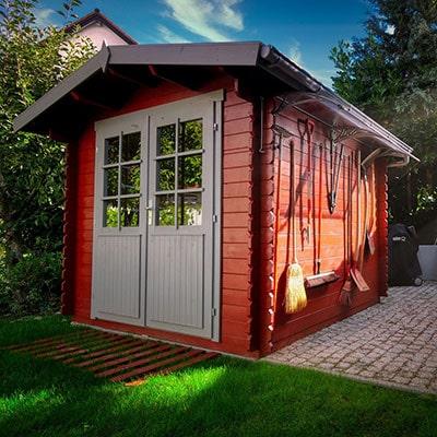 a wooden shed with tools hanging on the wall