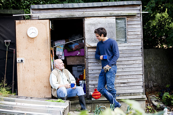 two gardeners chatting in front of a shed by an allotment