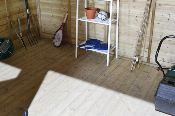 wooden shed floor close up with several tools, shelves and mower visible