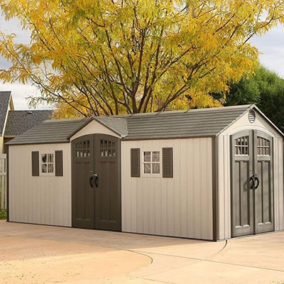 large plastic shed in shades of grey with window shutters and windowed doors