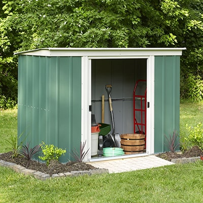 a green and white metal pent shed with open sliding doors in a garden setting with tools visible inside