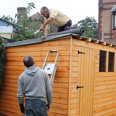 man on top of wooden shed applying felt with another man in the garden watching