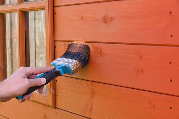 hand holding a large paint brush applying shed treatment to a wooden shed
