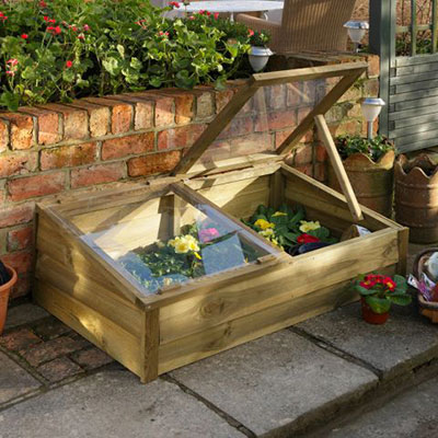 a wooden cold frame with one lid propped open