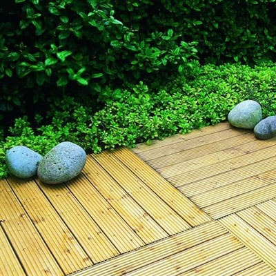 wooden deck tiles edged by greenery and stones