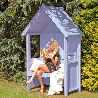 a woman reading in a blue-painted garden arbour
