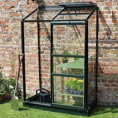 a lean-to greenhouse with a green frame and open roof vents