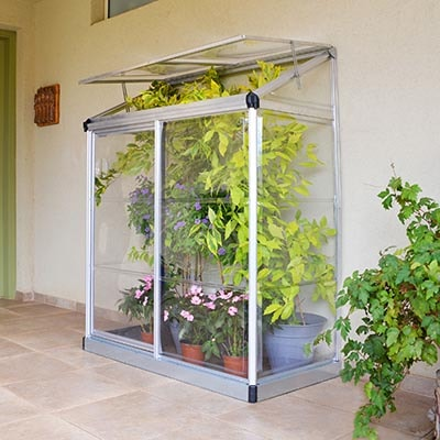 a silver-framed lean-to greenhouse full of plants