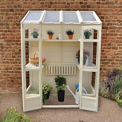 a cream-painted, wooden lean-to greenhouse with open doors