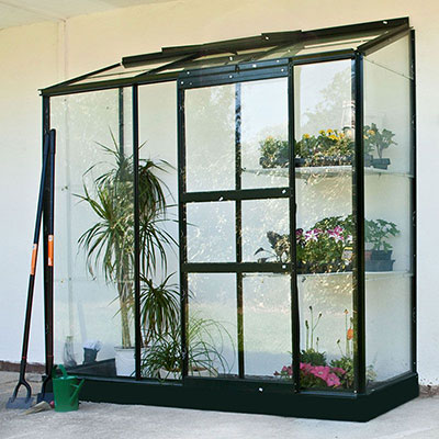 a lean-to greenhouse with a green frame