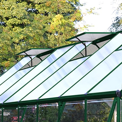 a greenhouse with a green frame and 2 open roof vents