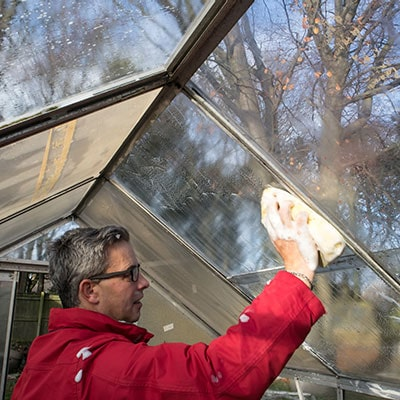 a man cleaning a greenhouse
