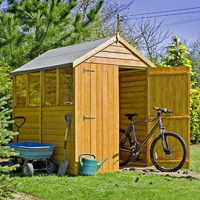 a wooden overlap shed with windows and the door open to show a bike all in a garden setting