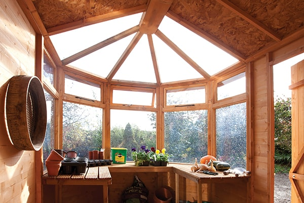 inside a Rowlinson potting shed showing windows, benches and accessories