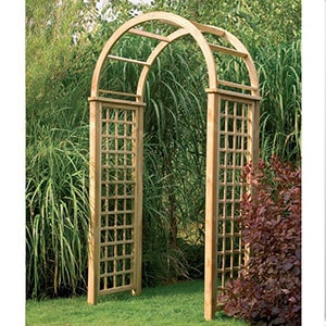 A wooden garden arch, with a trellis design, leading into another area of a garden.
