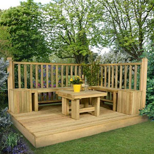 A wooden garden decking kit, including railings positioned at a right angle and a wooden garden table positioned on the decking boards.