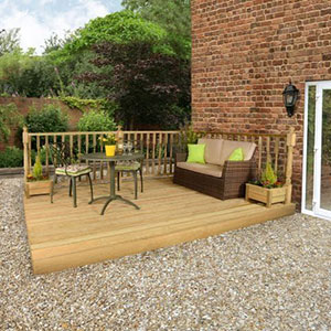 A sofa and garden table and chairs on top of a 3.6mx3.6m wooden garden decking kit with railings.