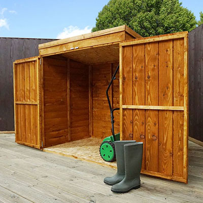 A wooden lawn mower storage shed with its double doors open to reveal a mower
