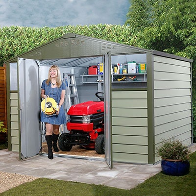 A woman stood outside a green, metal riding mower shed