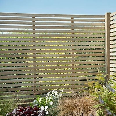A 5'11x5'11 slatted fence panel in a garden