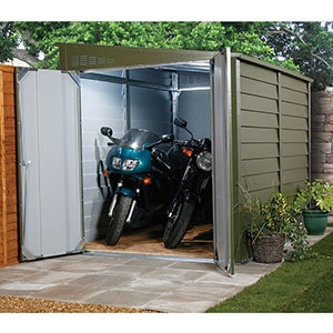 The 9x5 Trimetals Protect-a-Bike Secure Garden Storage, located in the corner of a garden, with its doors open to reveal 2 motorbikes.