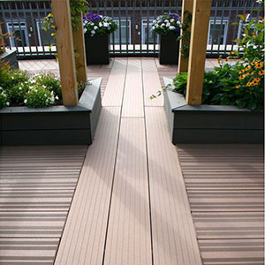 Brown composite deck boards leading out to a roof terrace, which is decorated with planters.
