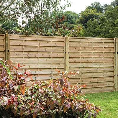 A run of pressure-treated decorative fence panels