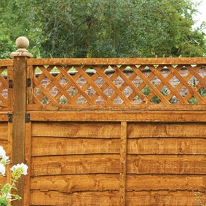 The Forest 6x1 Diamond Lattice Trellis Fence Topper, positioned on top of a wooden fence panel.