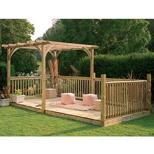 A garden decking kit, including railings and a pergola, situated on a lawn.