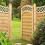 The Forest Paloma 3x6 Decorative Pressure Treated Garden Gate, with Paloma fence panels either side, opening to reveal a field and trees.