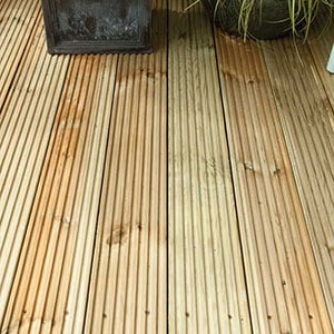 2 black plant pots on top of some wooden garden decking boards.