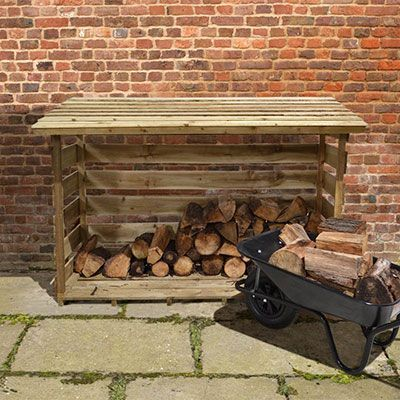 a wheelbarrow full of logs in front of an extra-large log shed