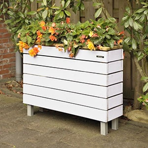 The white Hillhout Nova Rectangular Wooden Garden Planter 3x1, full of plants with orange flowers, situated on a patio.
