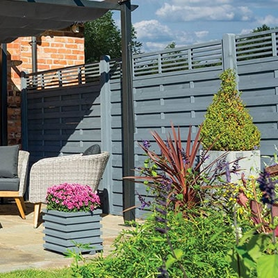A run of grey fence panels with slatted tops