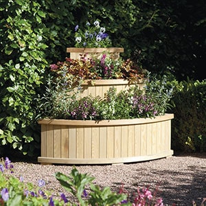 The Rowlinson Marberry Cascade Corner Wooden Garden Planter 4x3m, full of plants, situated on gravel, surrounded by shrubs.