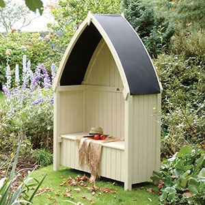 The cream Rowlinson Winchester Garden Arbour Seat 4x2, with its distinctive curved, black roof.