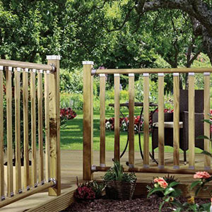 Wooden railings with chamfered deck spindles, at the edge of a wood deck, which leads to a lawn.