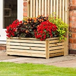 The Rowlinson Garden Creations Wooden Rectangular Planter 3x1, full of brightly-coloured flowers, situated on a patio, next to a house.