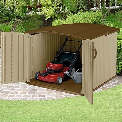A brown, plastic lawn mower storage shed containing a red lawn mower