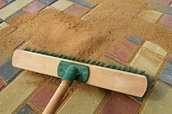 brushing sand into brick paving joints