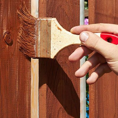 a hand holding a brush, applying wood preservative to a fence