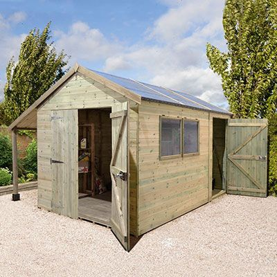 a large wooden shed with an apex roof, double doors, a separate single door, 2 windows and an integral log store