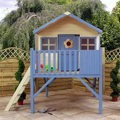 a cream and blue kids' playhouse on top a wooden tower, including a ladder