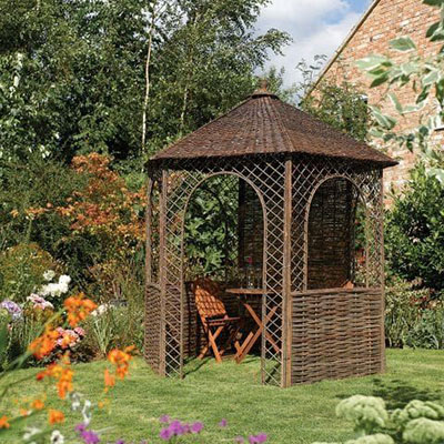 A small, hexagonal garden gazebo, made of willow and with part-trellis sides