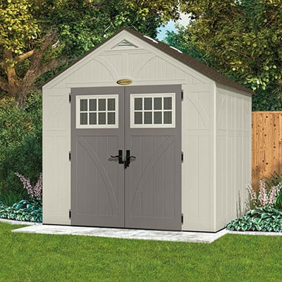 A cream and brown plastic shed with partially-glazed, grey double doors