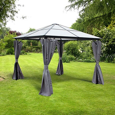A polycarbonate garden gazebo, with a pyramid-shaped roof, open sides and grey curtains tied to the corner posts