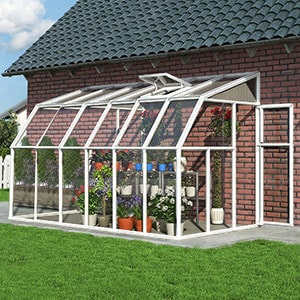 A white-framed lean-to greenhouse, positioned on a patio, in a July garden.
