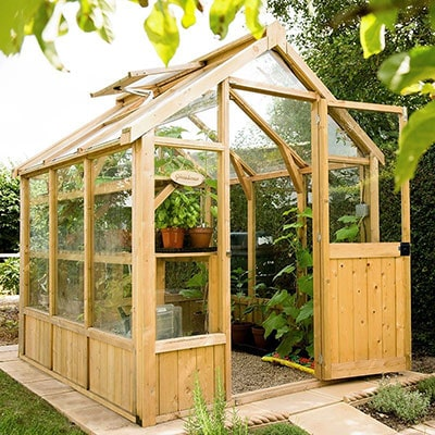 a wooden greenhouse with an open roof vent and sliding door