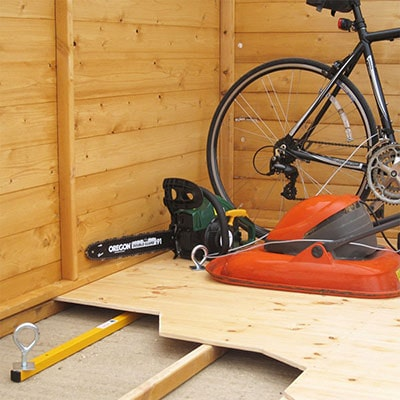 a bicycle, lawnmower and power tool, attached to a shed floor by an underfloor locking kit