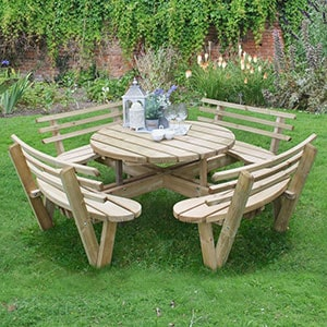 The Forest Circular Wooden Garden Picnic Table with Seat Backs, with cups and flowers on the table and situated on a lawn.
